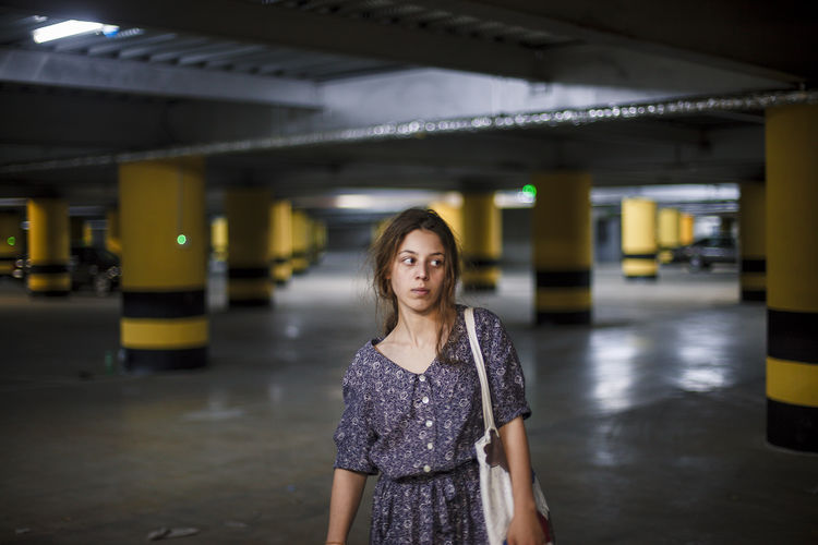 Young woman looking away while standing in parking lot