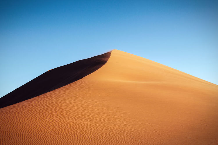 Low angle view of sand dune at namib desert against clear sky