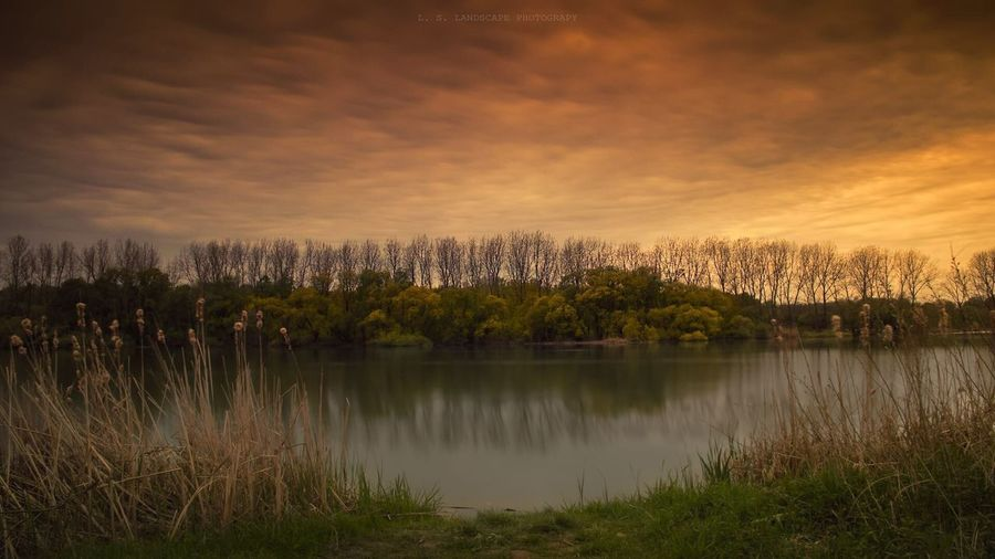 Scenic view of lake against sky during. sunset