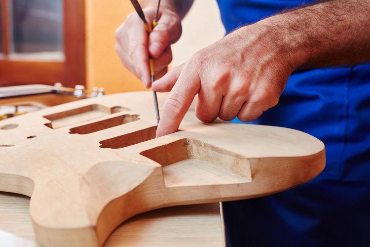 Midsection of worker making guitar at workshop
