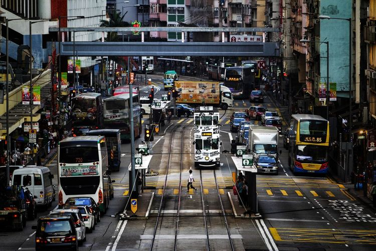 A woman crossing the street where tram is passing by, a typical scene in hong kong island.
