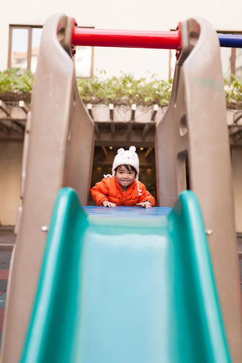 Portrait of girl on slide at playground
