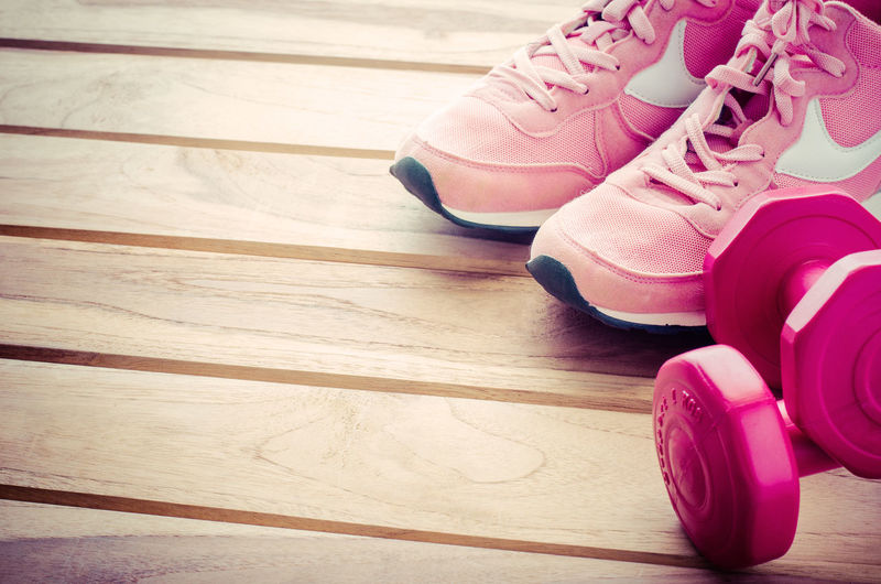 Shoes and dumbbells on wooden floor