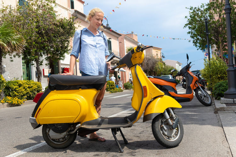 Full length of woman standing by scooter outdoors