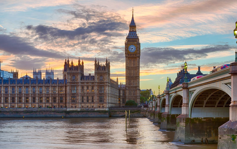Big ben and houses of parliament by thames river during sunset
