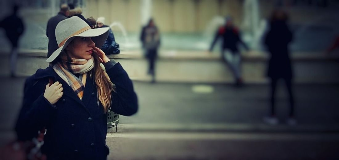 Young woman wearing hat standing on street