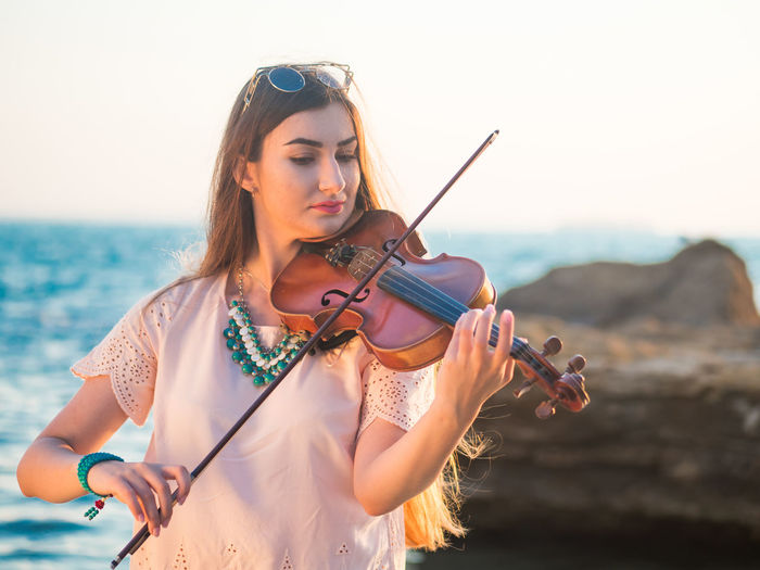 Young woman playing violin while by sea