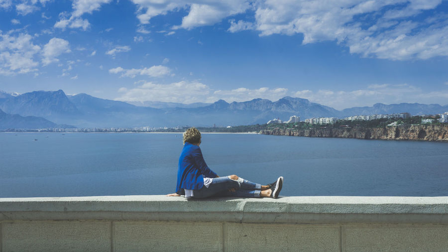 Man sitting on retaining wall by lake against sky