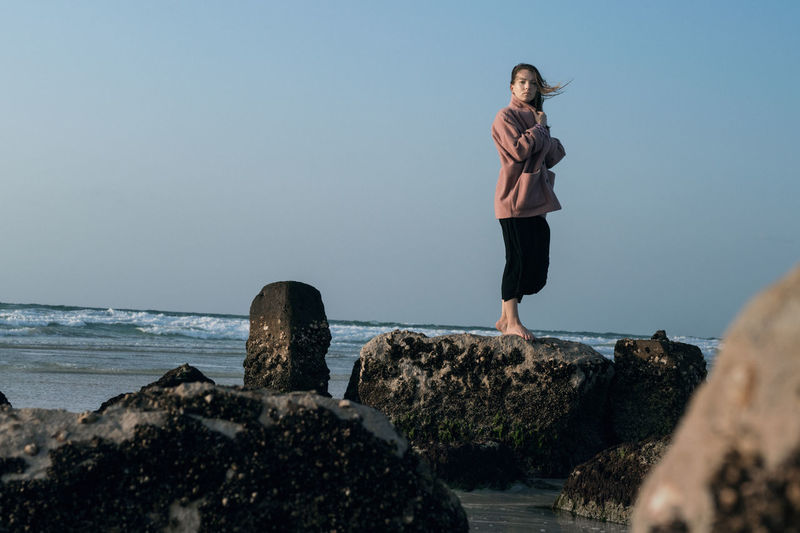 Woman standing on rock by sea against clear sky