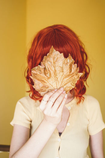 Woman with dry leaf standing against wall
