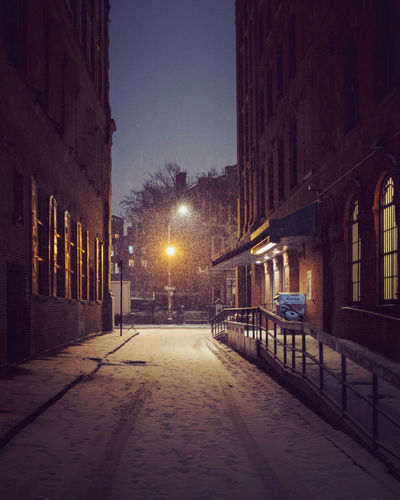 Street amidst illuminated buildings in city at night during winter