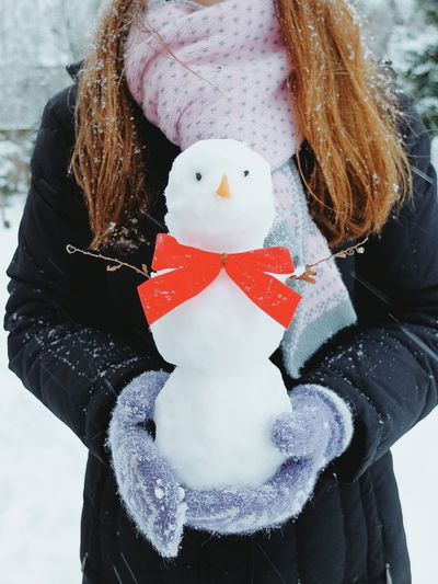 Midsection Of Woman Holding Snowman At Yard