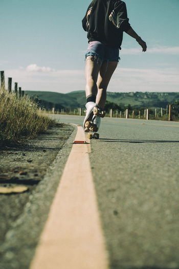 Surface level view of woman roller skating on road against sky