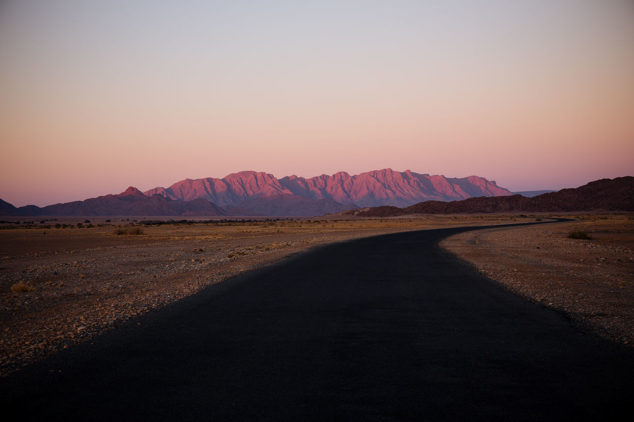 Empty road and mountains against clear sky during sunset