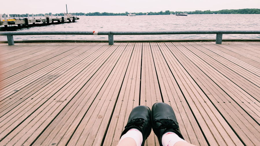 Low Section Of Person Relaxing On Pier Over River