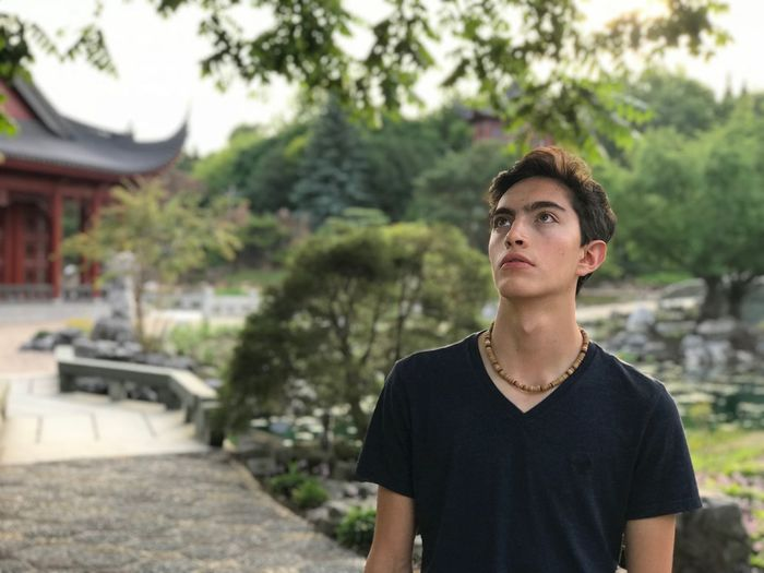 Handsome Young Man Looking Up While Standing Outdoors