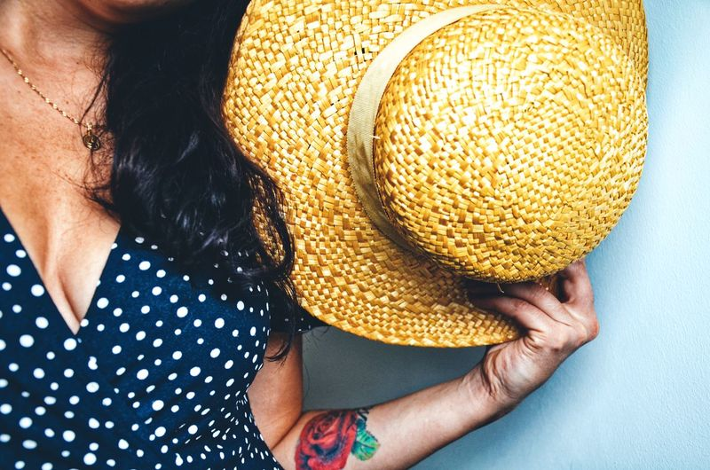 Midsection Of Woman Holding Hat Against Wall