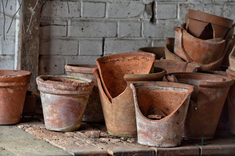 Broken flower pots on wooden table against brick wall