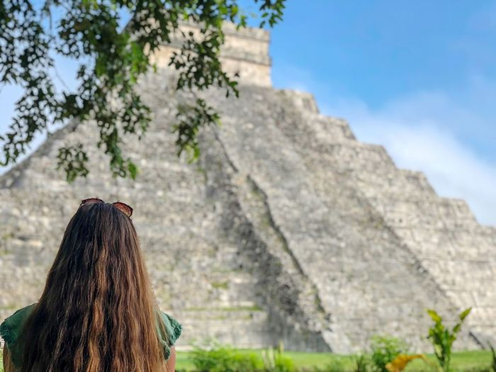 Temple of the maya . Chichen Itza Plant Tree Nature Focus On Foreground Day One Person Mountain Leisure Activity Sky Outdoors Rear View Lifestyles Women Beauty In Nature Low Angle View Cloud - Sky Land Real People Travel Destinations Hairstyle A New Perspective On Life EyeEmNewHere
