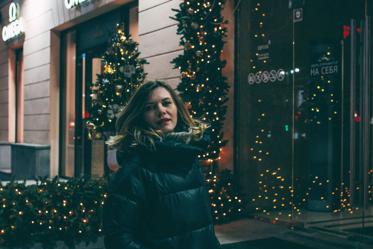Young woman standing by illuminated christmas tree at night