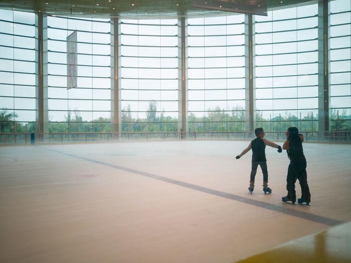 Full length of children ice skating against window