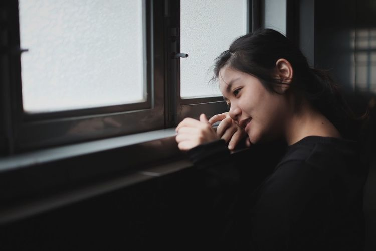 Portrait of woman sitting by window at home