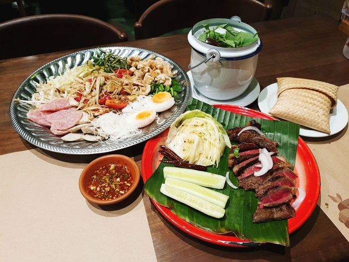 Papaya Salad big set with medium grilled meat slied cucumber and a bamboo container for holding cooked glutinous rice or Kratip. Thailand Thaifoods ThaiFoodGoodTaste Thaistyle Somtum Pu-plarha Grilled Meat Kratip Sticky Rice Tart - Dessert Plate SLICE Close-up Food And Drink Served