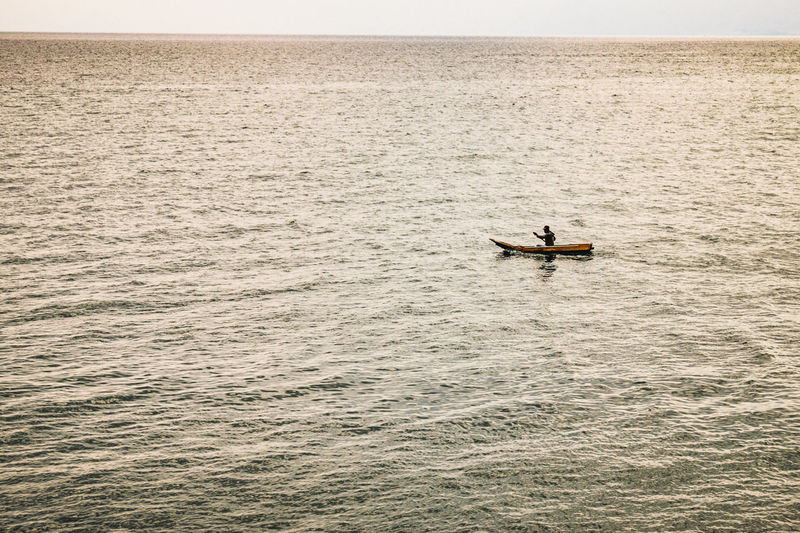 Man on boat in sea against sky