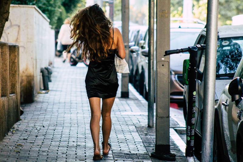 Rear view of woman walking on footpath in city