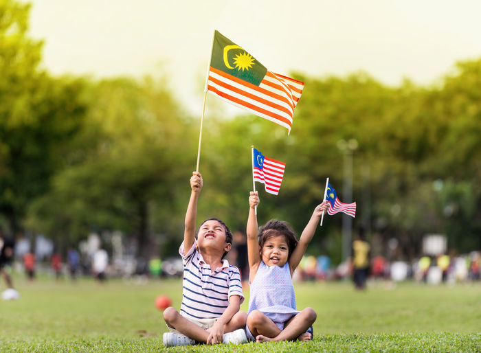 Cheerful siblings holding malaysian flags