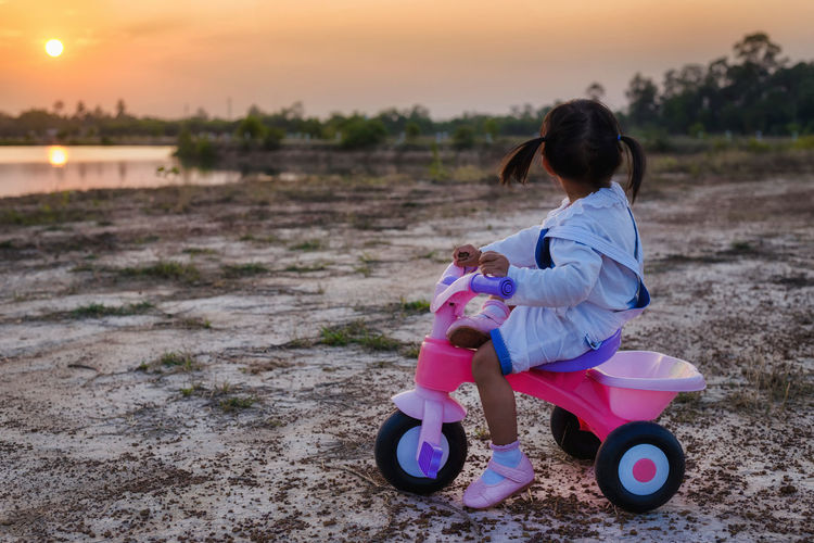 Full Length Of Girl On Tricycle At Beach Against Sky During Sunset