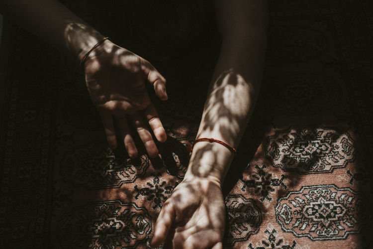 Cropped hands of woman on carpet