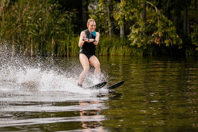 Full length of man splashing water in lake
