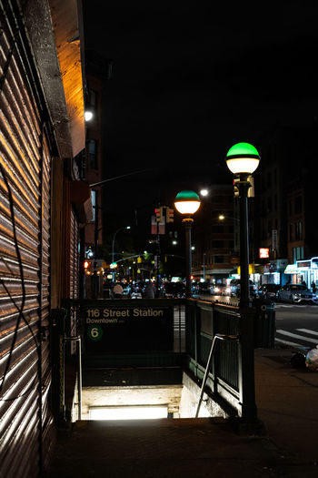 Illuminated street lights by buildings in city at night