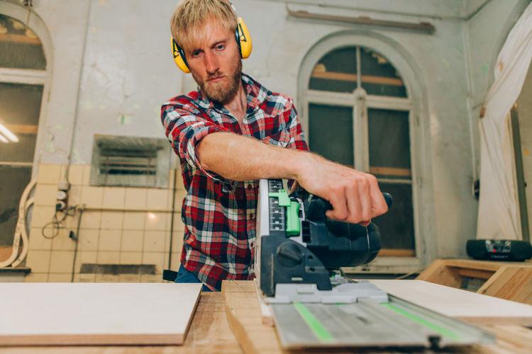 Carpenter man cutting wood with mowing saw using mowing saw
