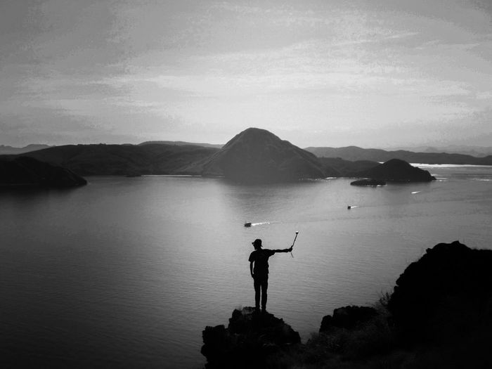 Silhouette man taking selfie while standing on rock against river during sunset