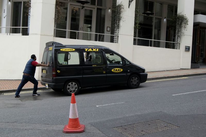 Architecture Transportation Built Structure Irony Humour People Full Length Adult Adults Only One Man Only Building Exterior Occupation City Day Streetphotography Digitalphotography 50mm Birmingham Modern Vibrance Candid Taxi Cone