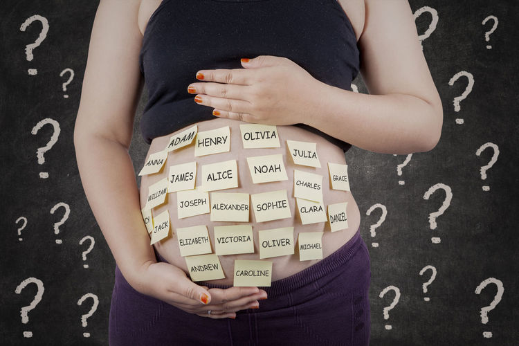 Midsection Of Pregnant Woman With Sticky Notes On Abdomen