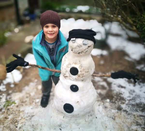 Portrait Of Boy Standing By Snowman