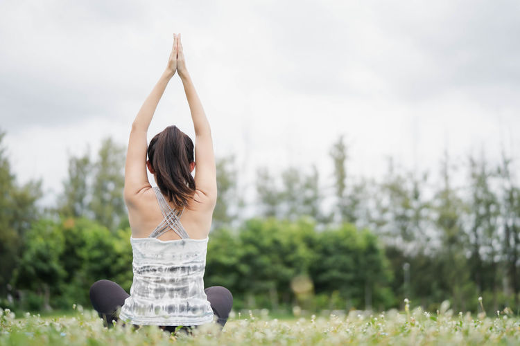 Woman with arms raised against plants