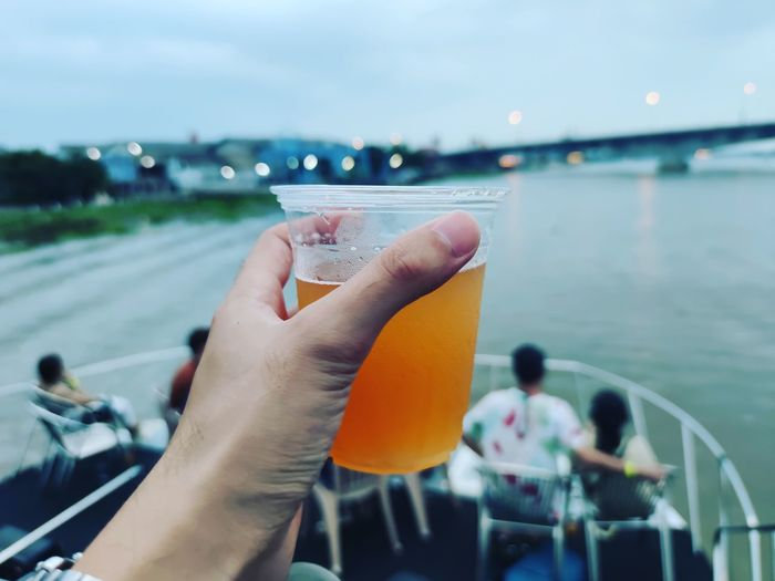 Cropped hand of man holding drink on boat