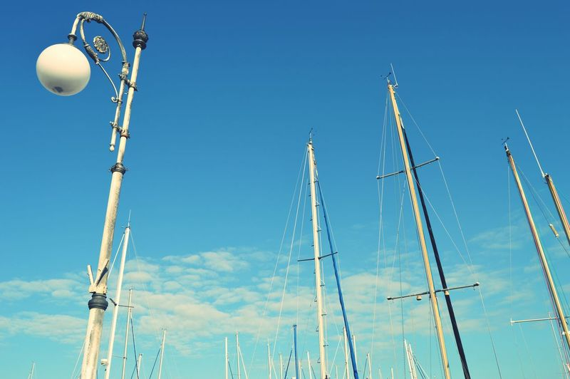 Low angle view of lamp post and masts against blue sky