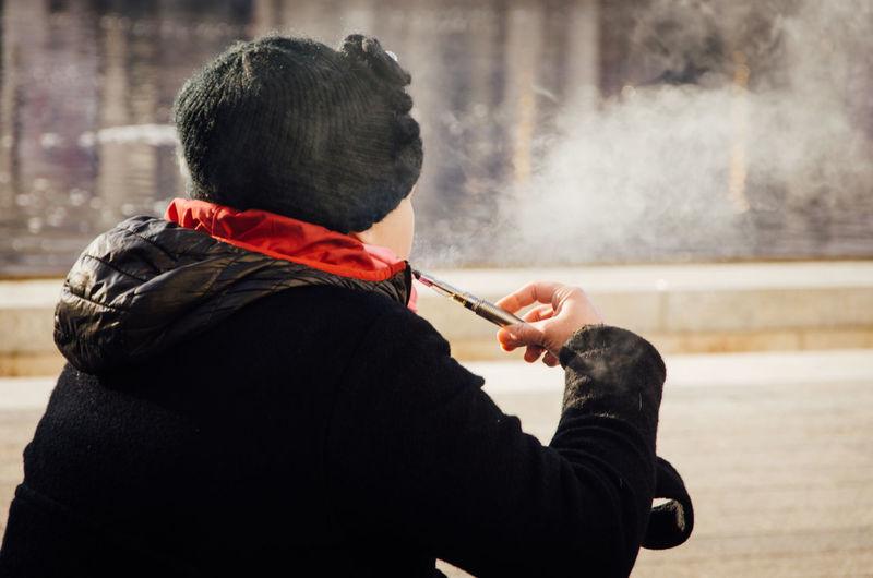 Rear View Of Woman Smoking E-Cigarette