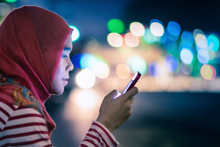Profile Of Young Woman Using Phone At Night