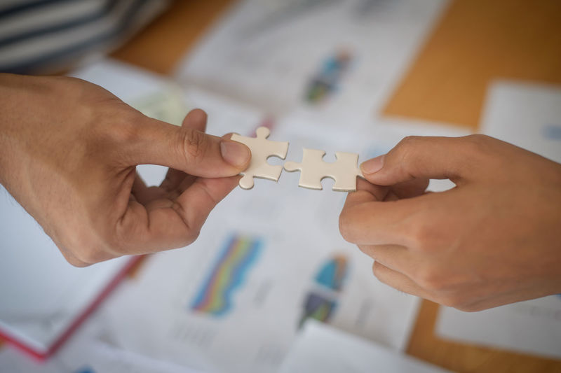 High Angle View Of People Holding Jigsaw Piece On Table