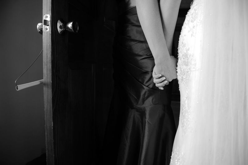 Midsection of bride and friend holding hands at doorway