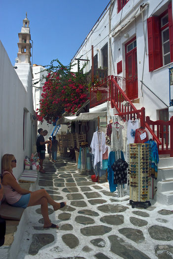 colored street view of Mykonos with woman sitting to relax in front of a souvenirs shop Built Structure Architecture Building Exterior Real People Women City Group Of People Day Building Men Lifestyles Leisure Activity People Adult Street Nature Casual Clothing Outdoors Child Incidental People Sitting Shops Souvenirs/Gift Shop Bouganville Flower Red Windows Greek Architecture White Buildings Mykonos,Greece Streetphotography Street View Travel Travel Destinations Summertime Shopping