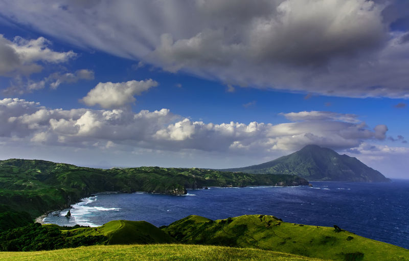 A view or racuh a payaman in Batanes Philippines Marlboro Country Philippines Racuh A Payaman Batanes Beauty In Nature Cloud - Sky Day Environment Green Color Idyllic Land Landscape Mountain Nature No People Non-urban Scene Outdoors Plant Scenics - Nature Sea Sky Tranquil Scene Tranquility Water