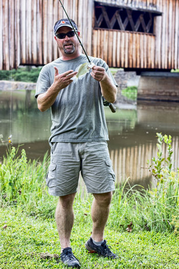 Man caught a fish full view Casual Clothing Day Fish Fishing Front View Full Length Glasses Holding Holding Fish Lake Leisure Activity Lifestyles Males  Man Caught A Fish Men Nature One Person Outdoors Plant Shorts Smiling Standing Sunglasses Water
