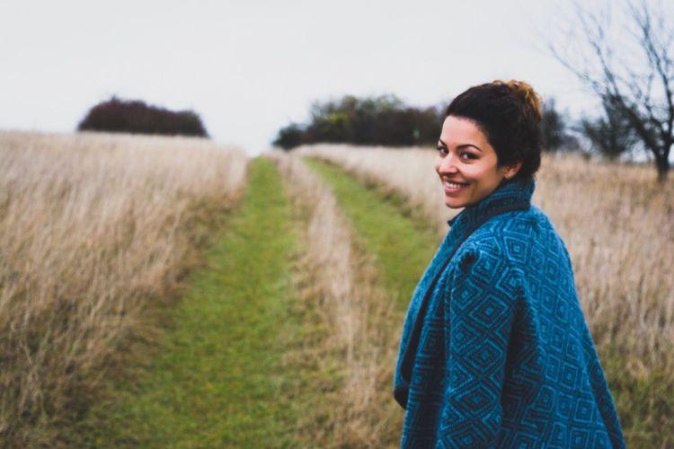 Portrait of woman standing on grassy field